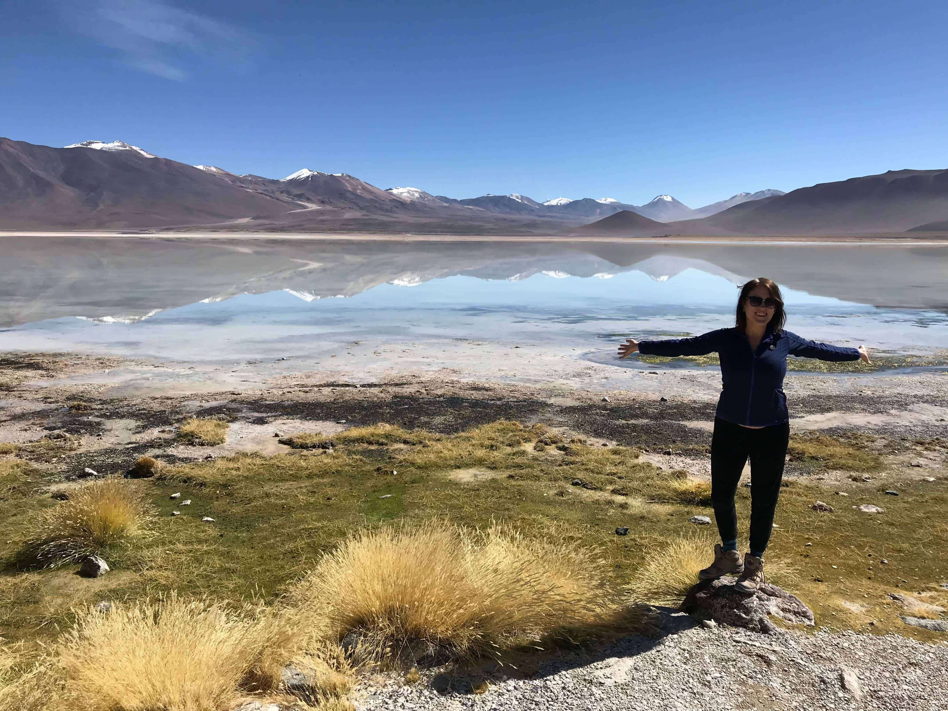 lora standing in front of Reflecting mountains and lakes in Bolivia