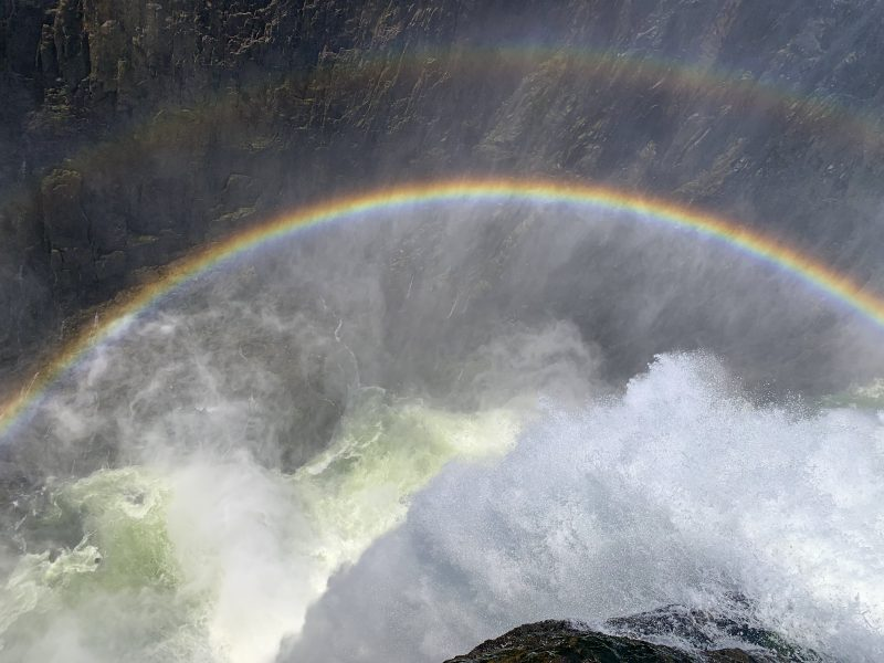 Looking over victoria falls on devil's pool in Victoria falls, one of the most popular tour