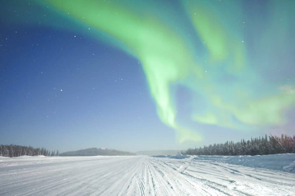 northern lights dancing above the ice road in yellowknife