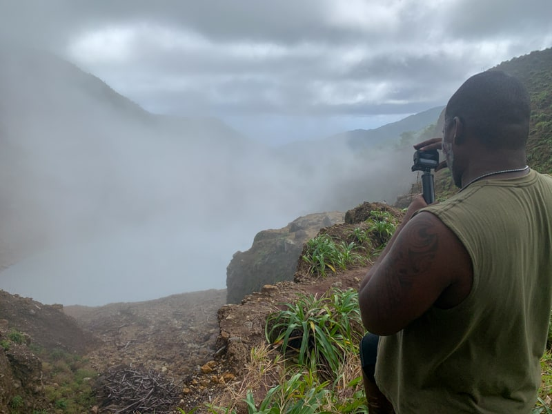 man taking a photo of boiling lake