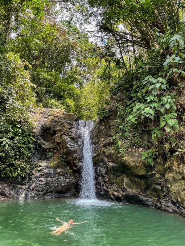 girl swimming under waterfall