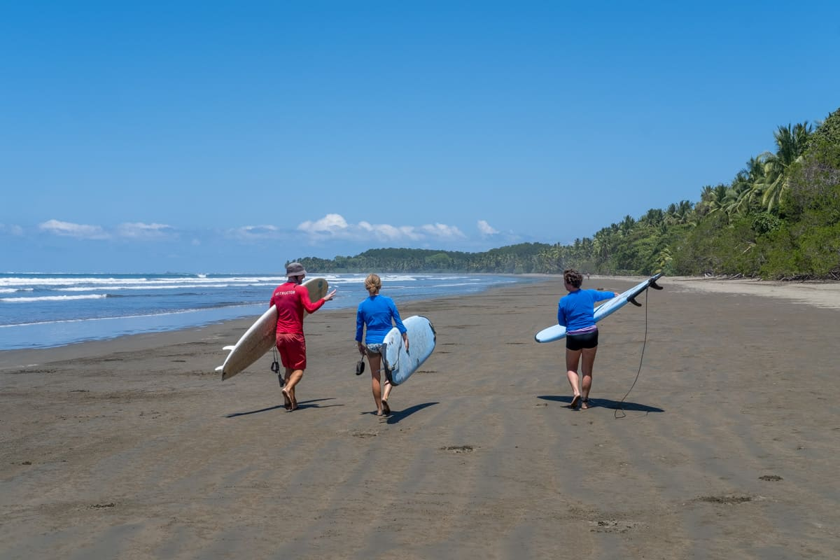 people walking with surf boards
